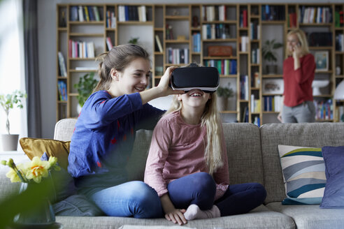 Sisters sitting on couch, playing with VR glasses - RBF06257