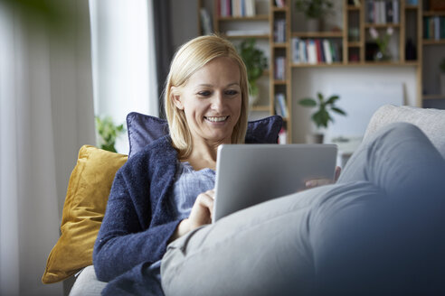Woman using digital tablet, relaxing on couch - RBF06266