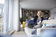 Woman relaxing at home, sitting on couch - RBF06269