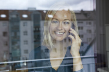 Blond woman standing at window, talking on the phone - RBF06278