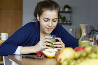 Girl sitting in kitchen, drinking homemade fruit smoothie - RBF06281