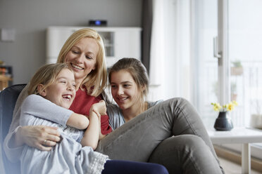 Happy mother and daughters having fun at home - RBF06296