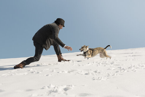 Man playing with dog in winter, having fun in the snow - REAF00270