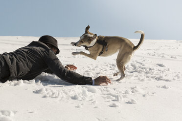 Man playing with dog in winter, lying on snow - REAF00273