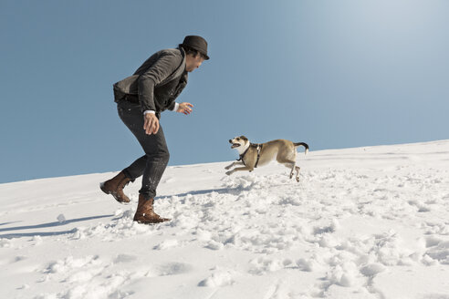 Man playing with dog in winter, throwing snow - REAF00276