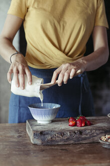 Woman preparing muesli, pouring yogurt in bowl, fresh strawberries - ALBF00344