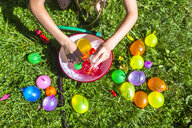 Girl preparing water bombs on a meadow - SARF03774