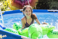 Portrait of smiling girl with swim toy in paddling pool - SARF03777