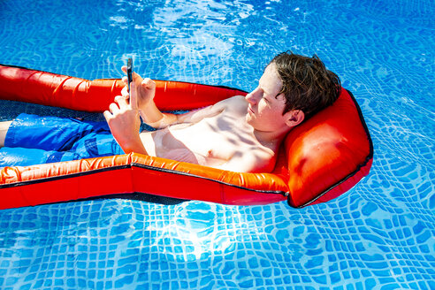 Boy floating on water in swimming pool using smartphone - SARF03780