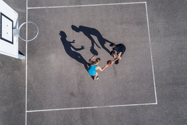 Young man and woman playing basketball, aerial view - STSF01607