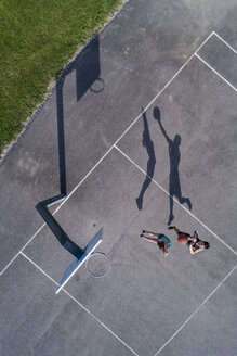 Young man and woman playing basketball, aerial view - STSF01610