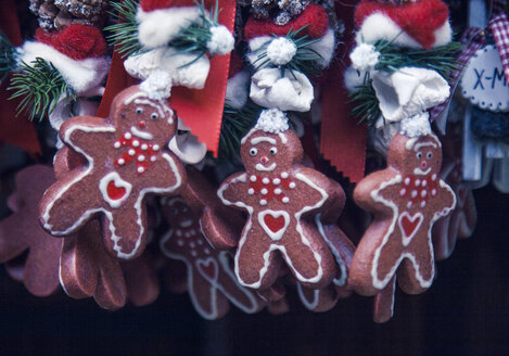 Close up of gingerbread men xmas decorations on German Christmas market stall - CUF28315