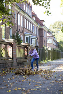 Girl sweeping leaves on pavement - JFEF00875