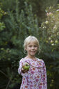 Portrait of smiling girl offering an apple - JFEF00878
