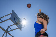 Young woman playing basketball, against the sun - STSF01612