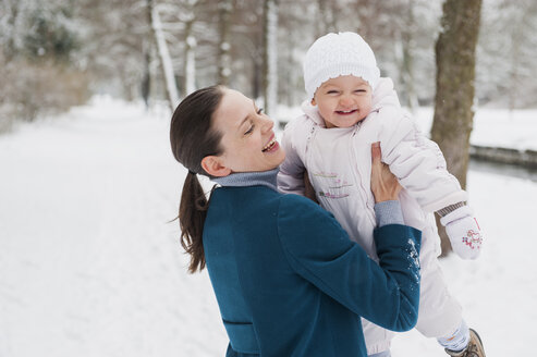 Portrait of happy baby girl having fun with her mother in snow-covered landscape - DIGF04570