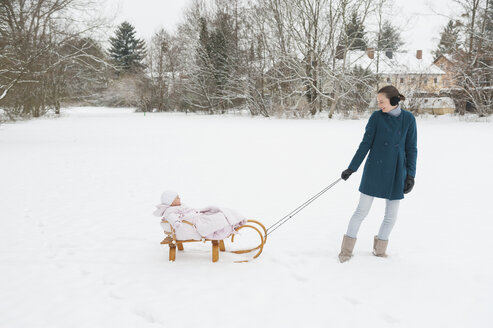Mother pulling little daughter on sledge - DIGF04573