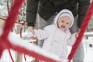 Portrait of smiling baby girl with father on playgroud in winter - DIGF04579