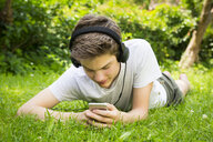 Boy lying on meadow listening music with headphones and smartphone - LVF07078