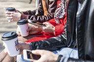 Russia, Moscow, details of three friends holding smartphones and coffee to go - WPEF00402