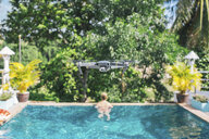 Flying drone over the swimming pool, woman in the background - MOMF00443