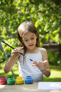 Girl in garden painting her hand with blue clour - LVF07080
