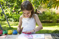 Smiling little girl printing colour on sheet of paper with her hand - LVF07083