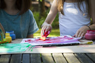 Two girls painting at table in the garden, partial view - LVF07086