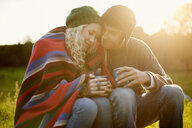 Romantic young camping couple wrapped in blanket with tea drinks - CUF28630
