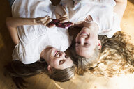 Two teenage girls lying on wooden floor reading smartphone texts - CUF28642