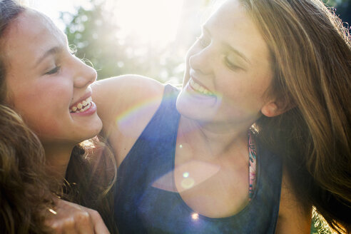 Close up of two teenage girls in sunlit park - CUF28648