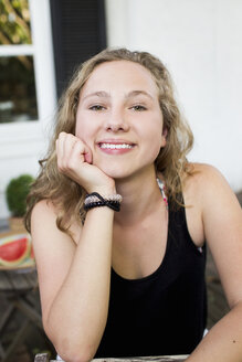 Portrait of happy teenage girl on patio - CUF28651