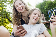 Two teenage girls reading smartphone texts in garden - CUF28654