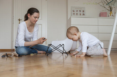 Mother and daughter assembling a chair at home - DIGF04588