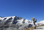Austria, Carinthia, man, hiker with binoculars watching Grossglockner peak, High Tauern National Park - GWF05535
