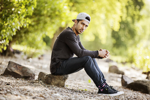 Portrait of young man with baseball cap sitting in nature - JATF01042