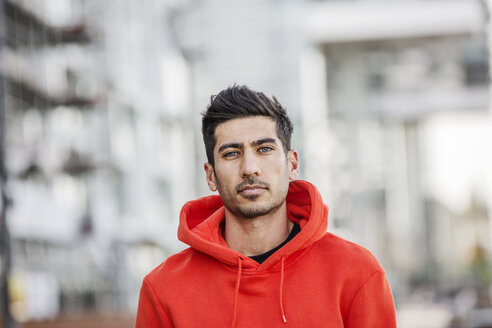 Portrait of fashionable young man wearing red hooded jacket - JATF01045