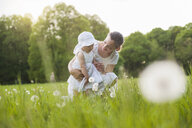 Mother and daughter with blowball on meadow in summer - DIGF04590