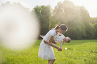 Mother and daughter playing on meadow in summer - DIGF04593