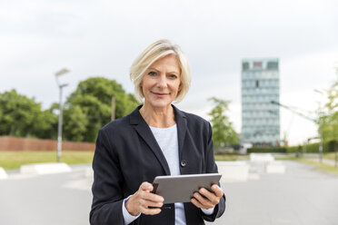 Portrait of confident senior businesswoman with tablet outdoors - FMKF05136