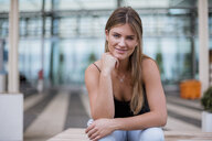 Portrait of smiling young woman sitting outdoors - DIGF04603