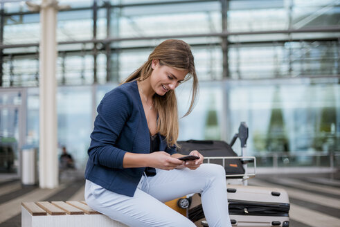 Smiling young businesswoman sitting outdoors with cell phone and suitcase - DIGF04606