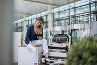 Smiling young businesswoman sitting outdoors with cell phone and suitcase - DIGF04609