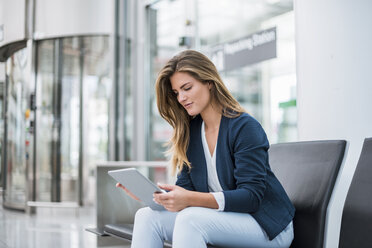 Young businesswoman sitting at waiting area using tablet - DIGF04624