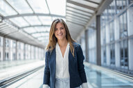 Portrait of smiling young businesswoman on moving walkway - DIGF04627