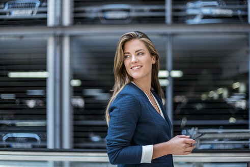 Portrait of smiling young businesswoman with cell phone in front of blurred parking garage - DIGF04630