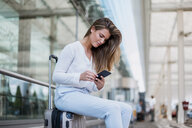 Young businesswoman sitting outdoors on luggage using cell phone - DIGF04633