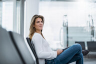 Young businesswoman sitting at waiting area with tablet - DIGF04639