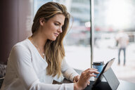 Young businesswoman in a cafe using tablet - DIGF04645