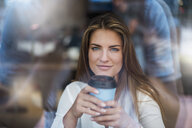 Portrait of smiling young woman behind windowpane with takeaway coffee - DIGF04648